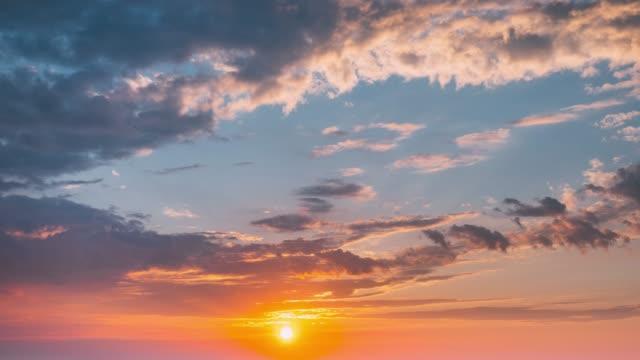 sunrise sky. heller dramatischer himmel mit fluffy clouds. gelb, orange, blau und magenta-farben - sonnenaufgang stock-videos und b-roll-filmmaterial