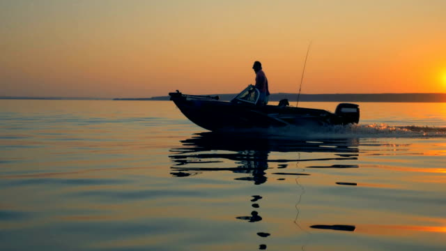 sunrise waterscape with a fishing boat and two people in it - andare in barca a vela video stock e b–roll