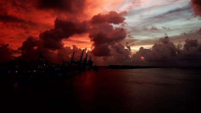 vídeos de stock e filmes b-roll de sunrise where the sky turned red. over looking miami loading cranes - apocalipse
