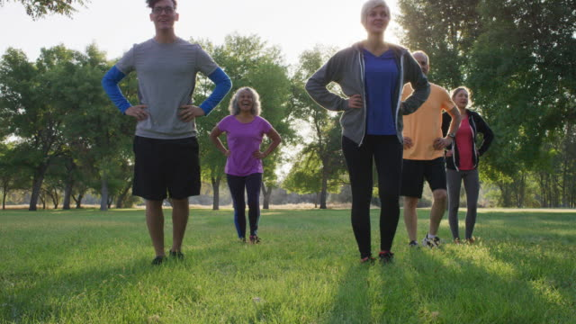 Sunrise workout group Diverse group of adults of various ages and ethnicities  working out at sunrise in a park 20 29 years stock videos & royalty-free footage