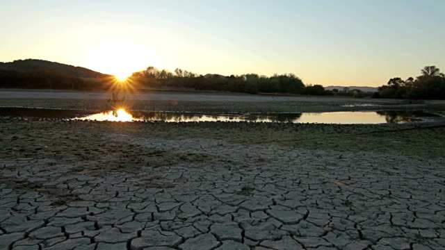 Sunset above drought disaster, dry soil. Climate change, global warming video