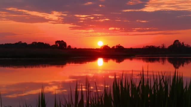 Sunset above the pond with cloudy sky at summer.