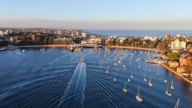 Sunset aerial drone footage of a fast ferry arriving from Sydney CBD (Circular Quay), docking at Manly Wharf pier - a 20 minute ride from the city. Manly is a beach-side suburb of Sydney, Australia.