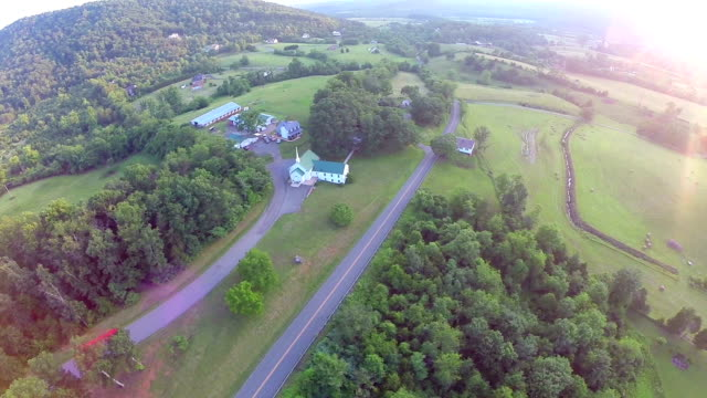 sunset aerial flyover of church with lens flare video