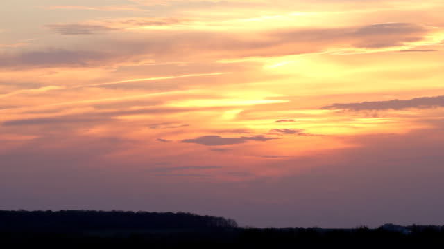 Sunset and clouds flying on red sky time-lapse video