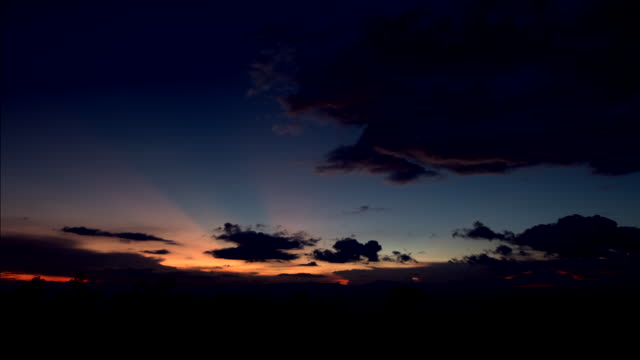 Sunset and clouds motion passing over mountain, Time lapse video