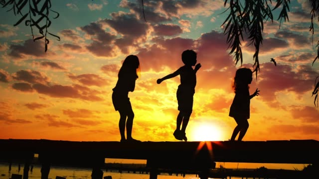 solnedgång och silhuetter av glada barn hoppar på träpiren ovanför sjö vattnet - flod vatten brygga bildbanksvideor och videomaterial från bakom kulisserna