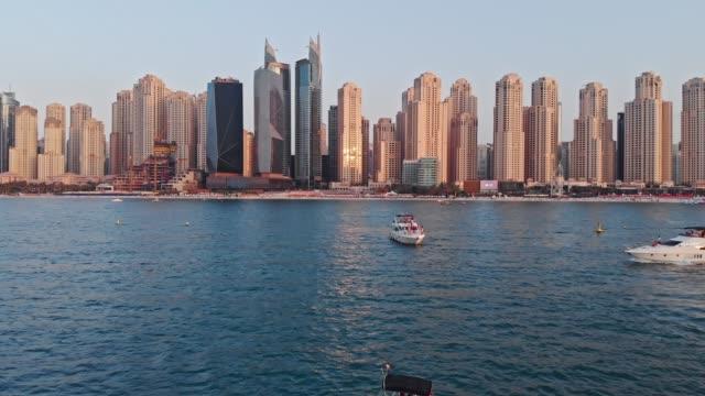 vídeos de stock, filmes e b-roll de pôr do sol na marina dubai e dubai eye drone vista com barco e pessoas - marina
