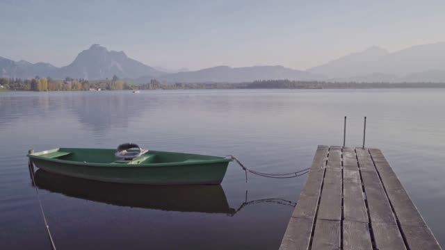 sunset at lake hopfensee in the allgäu alps - molo video stock e b–roll