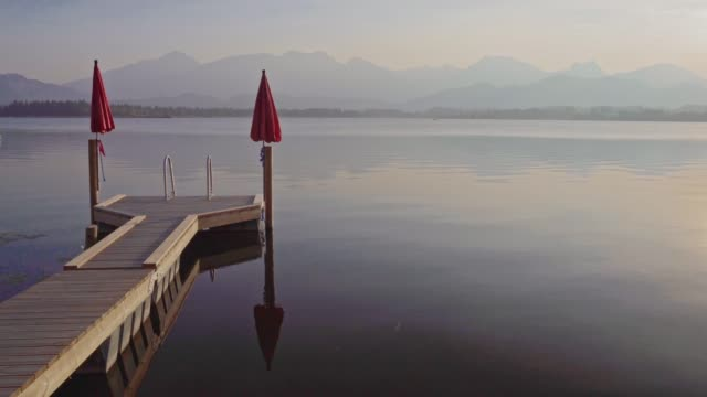 stockvideo's en b-roll-footage met zonsondergang in lake hopfensee in de allgäuer alpen - pier