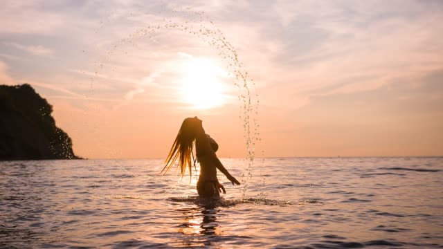 Sunset at sea, woman having fun on tropical vacation, splashing water with hair