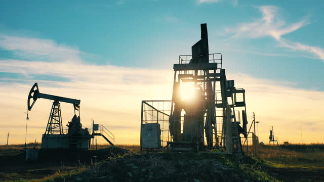 Sunset at the oil pumping site with multiple pumpjacks video