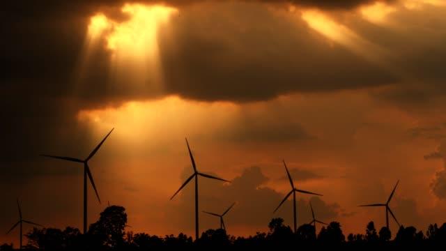 sunset at wind turbine power generator farm.