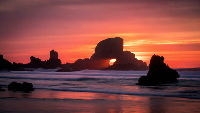 Sunset behind arch at Oregon coast USA video