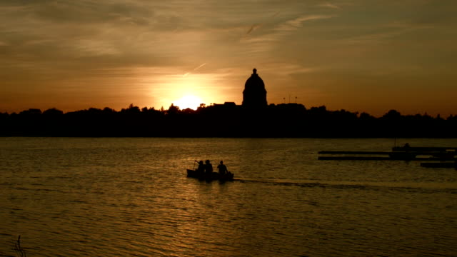 Sunset canoeing on lake in front of government building video