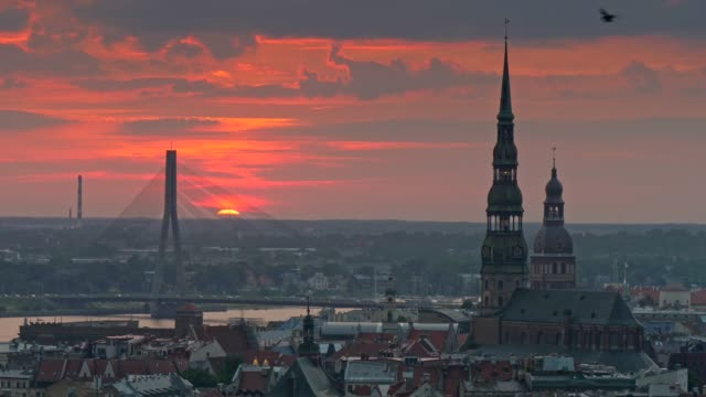 sunset cityscape of riga, latvia. car traffic on a stone bridge,  town hall and the old city. 4k, uhd - латвия стоковые видео и кадры b-roll
