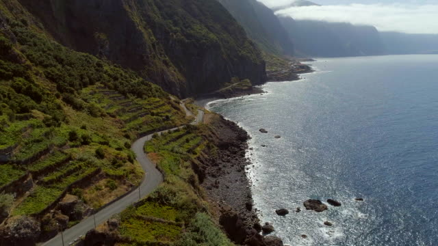 Sunset Coastal Road in Madeira Madeira is a small Portuguese island, situated North of the Canary Isles in the Atlantic Ocean. The island boasts incredible scenery due to the volcanic landscape which creates vast and steep mountains across the 20 mile island. funchal stock videos & royalty-free footage