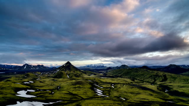 Sunset colors in sky clouds over green Icelandic mountains nature. Zoom in tilt up video
