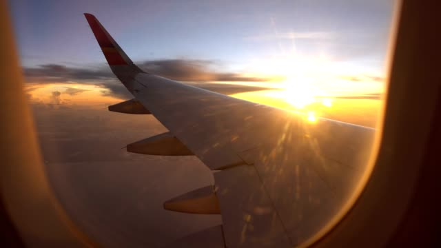 Sunset Flight and twilight sky with aircraft wing from an airplane window