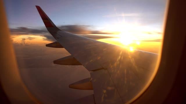 sunset flight and twilight sky with aircraft wing from an airplane window - skrzydło samolotu filmów i materiałów b-roll