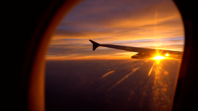 Sunset Flight with aircraft wing from an airplane window
