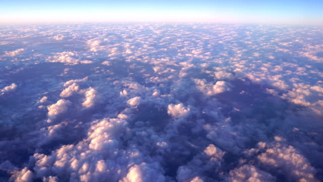 vídeos de stock e filmes b-roll de 4k sunset flying above the cloud sky in colorful from airplane window - above the clouds