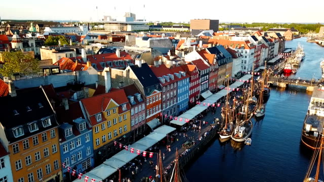 sunset footage video from copenhagen, denmark. nyhavn new harbour canal and entertainment district. aerial video footage view from the top. the camera rotates in a circle. sunset golden time light. - копенгаген стоковые видео и кадры b-roll
