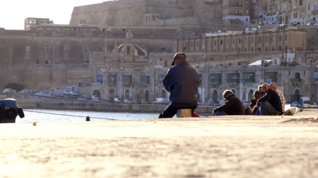 sunset in Malta: fishermen fishing with fishing rods at the port sunset in Malta: fishermen fishing with fishing rods at the port malta stock videos & royalty-free footage
