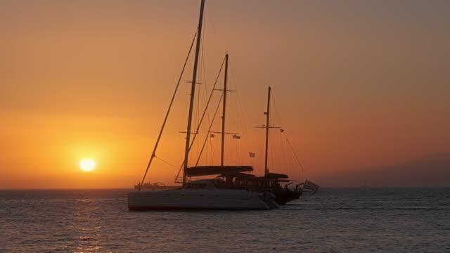 solnedgång i mykonos, grekland, med kryssningsfartyg och yachter i hamnen - egeiska havet bildbanksvideor och videomaterial från bakom kulisserna