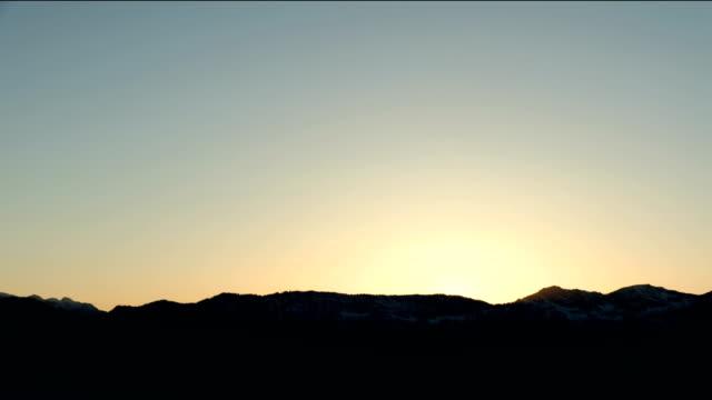 vídeos de stock e filmes b-roll de sunset in the mountains with the plains time lapse - linha do horizonte sobre terra
