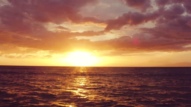 vídeos de stock e filmes b-roll de pôr do sol no oceano. vista aérea a voar baixo sobre oceano em dramático vibrante pôr do sol. - oceano pacífico