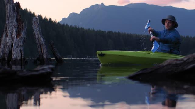 静かな山の湖パドリングスローモーションのサンセットカヤック旅行 ビデオ