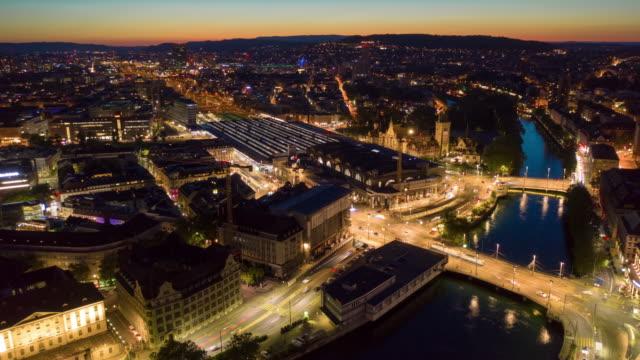 sunset night illuminated zurich city traffic train station square aerial panorama 4k timelapse switzerland video