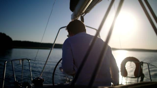 Sunset on a lake. Young man enjoying sailing