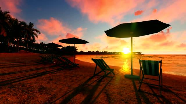 vídeos de stock, filmes e b-roll de pôr do sol sobre praia cheia de cadeiras e guarda-chuvas - estação turística