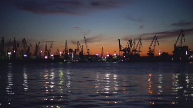 sunset over industrial cranes and cargo ships in varna port, bulgaria - bułgaria filmów i materiałów b-roll