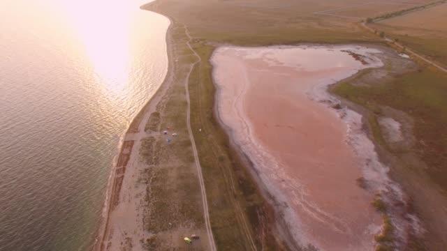 vídeos de stock, filmes e b-roll de antena: pôr do sol sobre a ilha em mar calmo - multicóptero