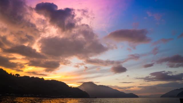 dağların üzerinden günbatımı - doğal koşul stok videoları ve detay görüntü çekimi