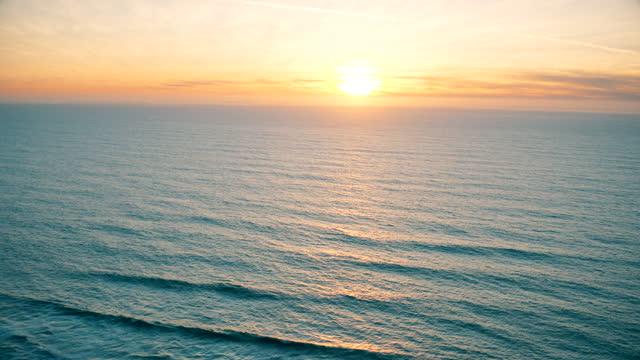 stockvideo's en b-roll-footage met zonsondergang over stille oceaan. luchtfoto's. - baai