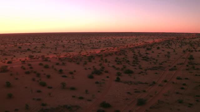 Sunset over sand dunes of the Kalahari desert An aerial shot of the sunset giving the red Kalahari desert a warm glow. namibia stock videos & royalty-free footage