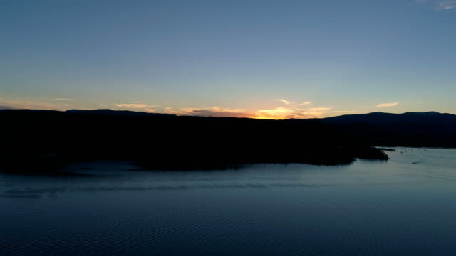 Sunset over scenic mountain lake from aerial drone video