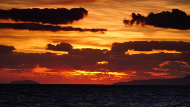 sunset over sea surface, dark clouds. time lapse - пелопоннес стоковые видео и кадры b-roll
