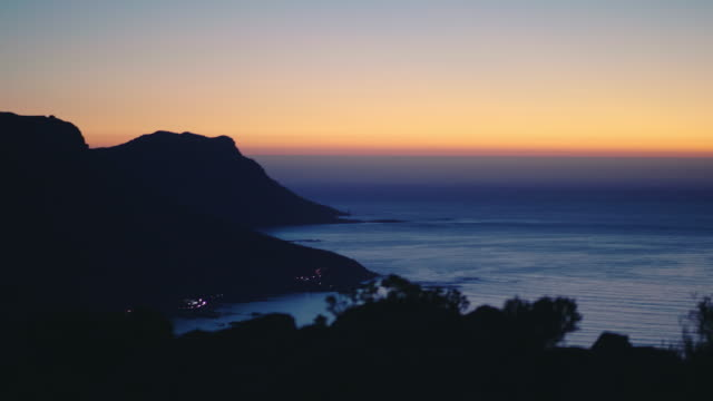 Sunset over South African Coastline Late sunset shot over the table top mountains and the South African coastline on a beautiful summer evening. Shot in 4K resolution. table mountain national park stock videos & royalty-free footage