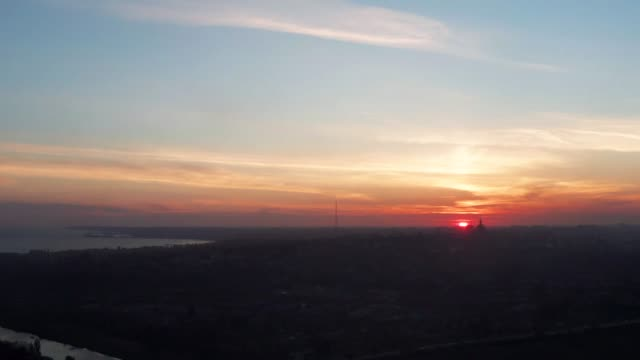 Sunset over the city. Silhouettes of buildings, sea and river Aerial video. Sunset over the city. Silhouettes of buildings, sea and river horizon over land stock videos & royalty-free footage