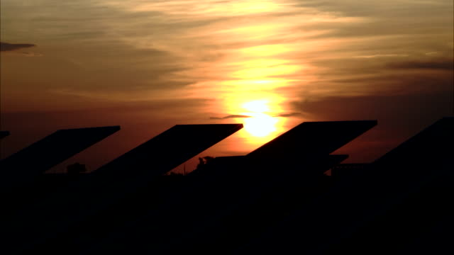 Sunset over the solar panels. Silhouettes of solar panels against the dark sky. video