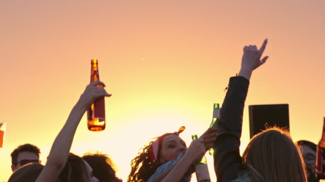 Sunset Party on Rooftop Group of multi-ethnic young people toasting with beer bottles and dancing to the music played by dj at sunset urban party on rooftop celebratory toast stock videos & royalty-free footage