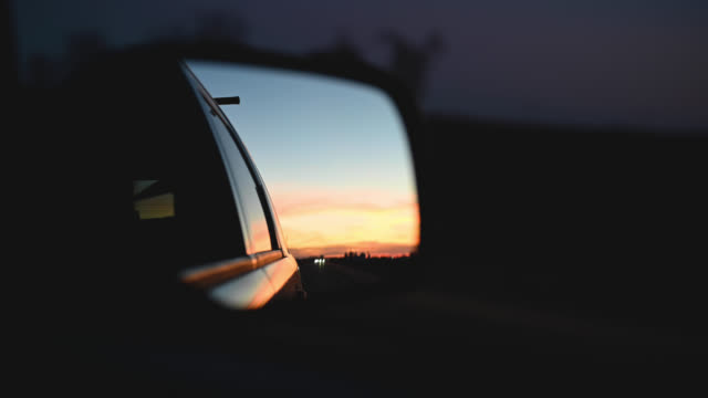 sunset reflected in car side view mirror
