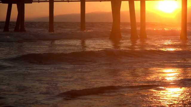 Sunset reflecting on the ocean waves under a pier Sunset reflecting on the ocean waves under a pier in slow motion b roll stock videos & royalty-free footage