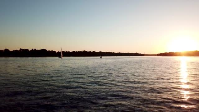 vidéos et rushes de reflet du coucher du soleil. vue aérienne de la côte de ake - lac reflection lake