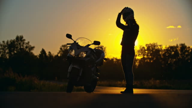 Sunset Ride Lady putting on motorcycle helmet and starting to ride at sunset work helmet stock videos & royalty-free footage